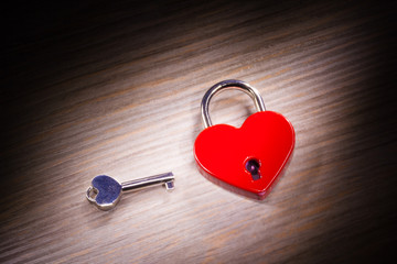 heart shaped closed lock on wooden background