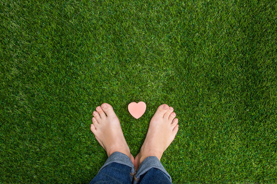 Mens feet standing on grass with small heart