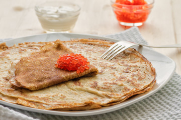 Baked pancakes with red caviar on a plate on a wooden table