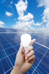 Solar energy panels and Light bulb in hand, Green energy concept