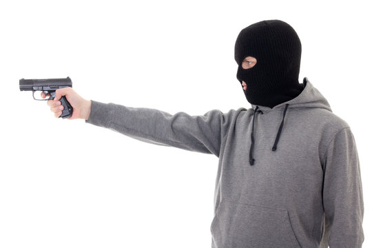 profile view of man in mask aiming with gun isolated on white