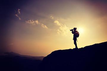 woman photographer taking photo on sunset seaside mountain peak