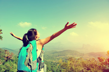 young woman hiker cheering open arms at mountain peak