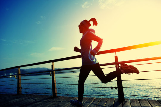 young fitness woman running on seaside boardwalk