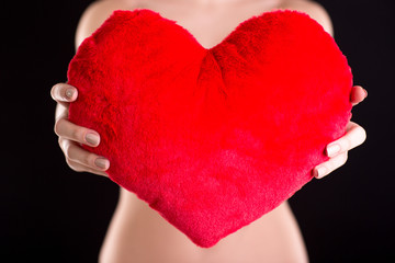 Closeup image of a woman holding red heart over black background