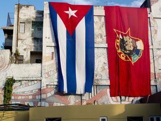 Immenses drapeaux cubains étendus sur un mur.