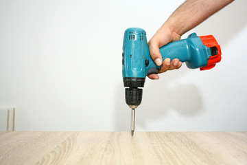 master working with drill over new kitchen cases