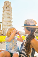 Baby girl taking photo of mother in front of tower of pisa