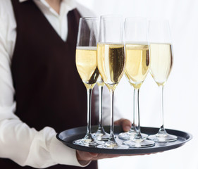 Professional male waiter in uniform serving champagne. DOF.