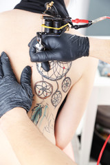 Tattooer showing process of making tattoo, close up