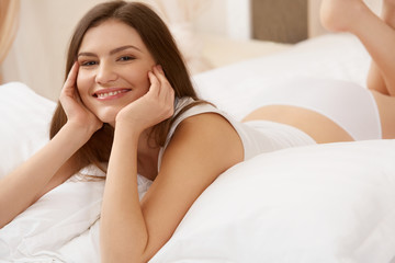 Portrait of a pretty woman relaxing in bed
