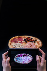Woman hands taking pictures of a pizza with a tablet