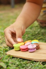 Hand were picked colorful of macaron on a brown tray