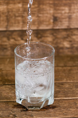 splash in water from a glass with ice, is isolated on a brown