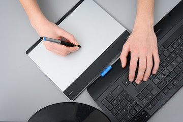 close up hands working with graphic tablet and keyboard