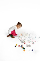 Little girl is drawing on white floor.