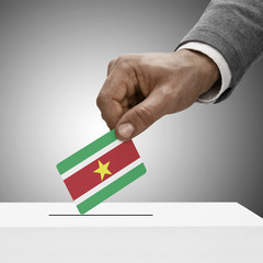 Black male holding flag. Voting concept - Surinam