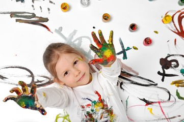 Little girl is playing with paints.