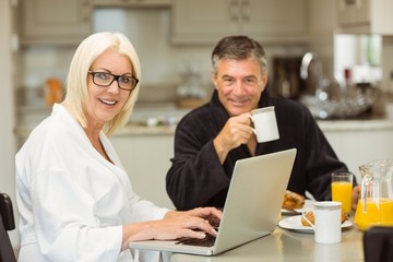 Mature couple having breakfast together woman using laptop