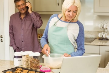Happy blonde preparing dough with husband behind