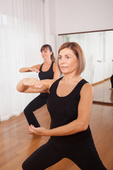 two women making a fitness exercisen in synchrony