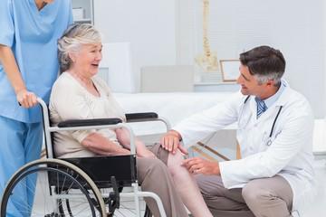 Doctor examining senior womans knee