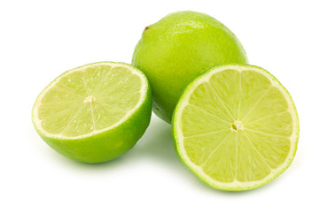 one whole lime fruit and two halves on a white background