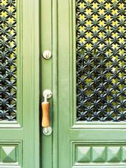 Green door with decorative grid