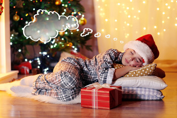 Little boy sleeping near fireplace in room and dreaming about