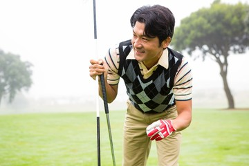 Golfer holding golf ball and club