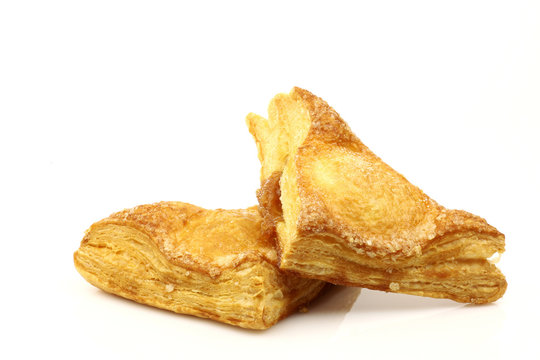 two freshly baked crispy apple turnovers isolated on white