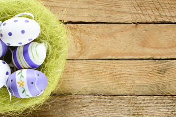 Decorated Easter eggs in nest on rustic wooden background