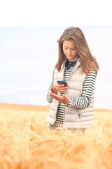 Young girl in field taking picture of wheat by smartphone