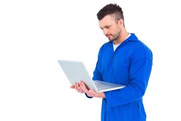 Happy mechanic using laptop