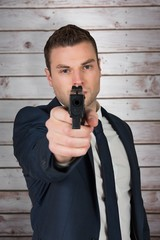 Composite image of serious businessman pointing a gun