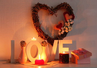 Romantic still life with wicker heart, word LOVE and candle