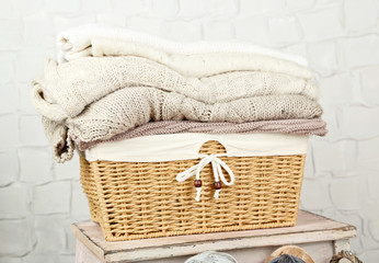 Knitting clothes in basket, on grey wool background