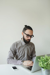 Man with beard in glasses typing laptop with smartphone