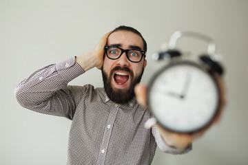 Man in panic holds alarm clock and head in fear of deadline