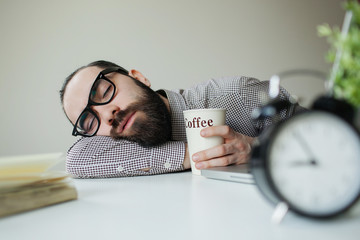 Man sleeps in office on table over laptop with coffee in hand