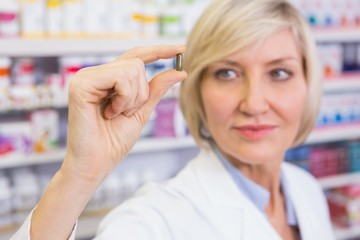 Blonde pharmacist in lab coats showing pill