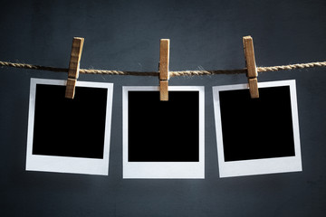 Blank polaroid photographs hanging on a clothesline