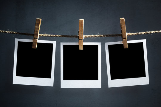 Blank polaroid photographs hanging on a clothesline