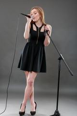 a beautiful blonde woman singing in microphone