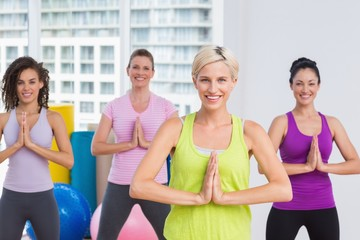 Women with hands joined exercising at gym