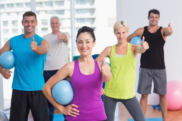 Instructor with class gesturing thumbs up at gym