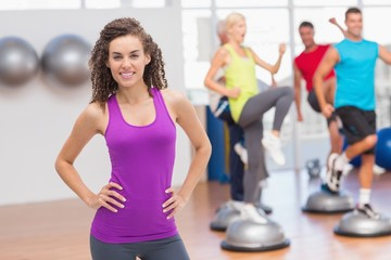 Happy fit woman standing hands on hips at gym