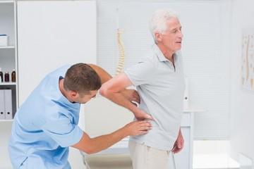 Physiotherapist giving back massage to senior man