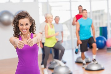 Happy woman gesturing thumbs up at gym