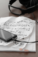 Closeup of smartphone with headphone on musical notes paper on w